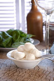Fresh Mozzarella cheese. With basil in the background Stock Photo