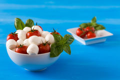 Fresh mozzarella, cherry tomatoes and basil in a bowl. Over a blue wooden background Royalty Free Stock Image