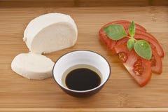Fresh mozzarella on chopping board with tomato Stock Photos