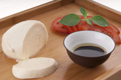 Fresh mozzarella on chopping board with tomato Royalty Free Stock Photography