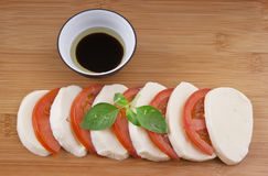 Fresh mozzarella on chopping board with tomato Stock Images
