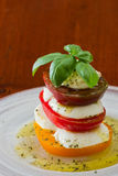 Fresh mozzarella and tomato salad. Stack of heirloom tomatoes with fresh mozzarella dressed with extra virgin olive oil and fresh green basil spiced with herbs Stock Image