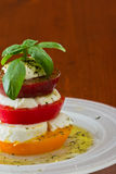 Fresh mozzarella and tomato salad. Stack of heirloom tomatoes with fresh mozzarella dressed with extra virgin olive oil and fresh green basil spiced with herbs Royalty Free Stock Images