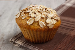 Fresh muffin with oatmeal baked with wholemeal flour on checkered tablecloth, delicious healthy dessert Stock Photos