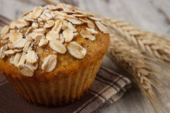 Fresh muffin with oatmeal and ears of rye grain on checkered tablecloth, delicious healthy dessert Stock Photo
