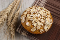Fresh muffin with oatmeal and ears of rye grain on checkered tablecloth, delicious healthy dessert Royalty Free Stock Images