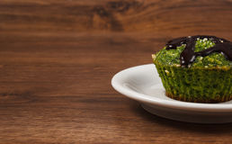 Fresh muffin with spinach, desiccated coconut and chocolate glaze, delicious healthy dessert, copy space for text Stock Image