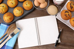 Cookbook for recipe with cake baking ingredients, copy space. Blank cookbook or writing book on a dark wood table with freshly baked muffins and ingredients Stock Photos