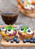 Fresh muffins with blueberry and cup of  coffee on wooden backgro Royalty Free Stock Images