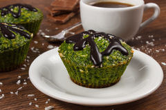 Fresh muffins with spinach, desiccated coconut, chocolate glaze and cup of coffee, delicious healthy dessert Stock Photo