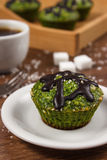 Fresh muffins with spinach, desiccated coconut, chocolate glaze and cup of coffee, delicious healthy dessert Royalty Free Stock Photos
