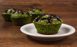 Fresh muffins with spinach, desiccated coconut and chocolate glaze, delicious healthy dessert Royalty Free Stock Photo