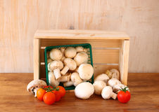 Fresh mufresh mushroom champignon in green rustic basket on wooden table. Royalty Free Stock Photo