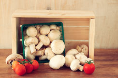 Fresh mufresh mushroom champignon in green rustic basket on wooden table Royalty Free Stock Image