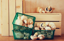 Fresh mufresh mushroom champignon in green rustic basket on wooden table. Stock Photos