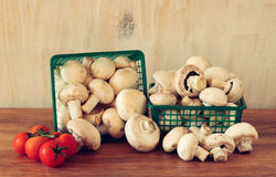 Fresh mufresh mushroom champignon in green rustic basket on wooden table. Stock Photography