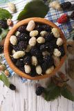 Fresh mulberry in a wooden bowl close-up. vertical top view. Fresh mulberry in a wooden bowl on the table close-up. vertical top view Royalty Free Stock Photo