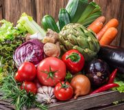 Fresh multi-colored vegetables in wooden crate. royalty free stock images