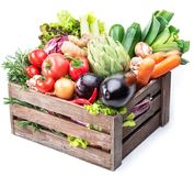 Fresh multi-colored vegetables in wooden crate. White background stock image