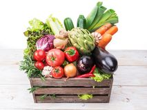 Fresh multi-colored vegetables in wooden crate. White background royalty free stock image