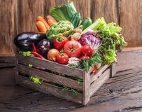 Fresh multi-colored vegetables in wooden crate. Wooden background. stock photo