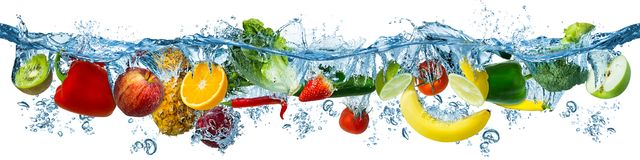 Fresh multi fruits and vegetables splashing into blue clear water splash healthy food diet freshness concept isolated white