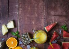 Fresh multifruit smoothie in a glass with fruits on a brown wooden rustic background, flat lay Stock Image