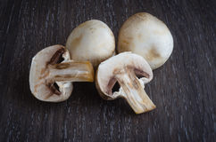 Fresh mushrooms champignons on wooden background. Stock Images