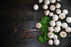 Fresh mushrooms champignons on the wooden texture desk with green spinach and different sorts of pepper. Appetizer concept Stock Images