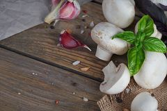 Fresh mushrooms and garlic. On wooden background Royalty Free Stock Photography