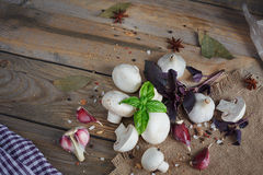 Fresh mushrooms and garlic on wooden background. Fresh mushrooms and garlic on rustic wooden background Stock Photo