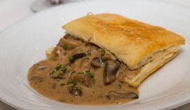 Fresh Mushrooms in Puff Pastry. A delicious appetizer of cooked mushrooms in a flaky puff pastry royalty free stock photos