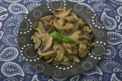 Fresh mushrooms. Some fresh mushrooms with basil on a black plate Stock Image
