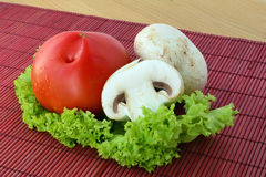 Fresh mushrooms with tomato. On green lettuce leaf Royalty Free Stock Photo