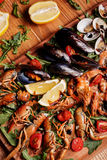 Fresh mussels, crayfish, shrimp. Seafood platter. Fresh mussels, crayfish, shrimp decorated with arugula, tomatoes, lemon and sauce on a wooden board. Seafood Stock Photos