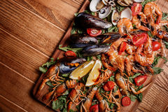 Fresh mussels, crayfish, shrimp. Seafood platter. Fresh mussels, crayfish, shrimp decorated with arugula, tomatoes, lemon and sauce on a wooden board. Seafood Royalty Free Stock Photography