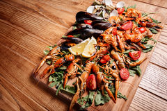 Fresh mussels, crayfish, shrimp on a wooden board. Fresh mussels, crayfish, shrimp decorated with arugula, tomatoes, lemon and sauce on a wooden board. Seafood Royalty Free Stock Images