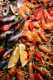 Fresh mussels, crayfish, shrimp on a wooden board. Fresh mussels, crayfish, shrimp decorated with arugula, tomatoes, lemon and sauce on a wooden board. Seafood Stock Photo