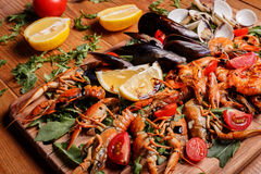 Fresh mussels, crayfish, shrimp on a wooden board. Fresh mussels, crayfish, shrimp decorated with arugula, tomatoes, lemon and sauce on a wooden board. Seafood Stock Photos