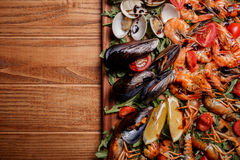 Fresh mussels, crayfish, shrimp on a wooden board. Fresh mussels, crayfish, shrimp decorated with arugula, tomatoes, lemon and sauce on a wooden board. Seafood Royalty Free Stock Photo