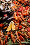 Fresh mussels, crayfish, shrimp on a wooden board. Fresh mussels, crayfish, shrimp decorated with arugula, tomatoes, lemon and sauce on a wooden board. Seafood Stock Photography