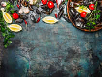 Fresh mussels with ingredients for cooking on rustic background, top view, border. Royalty Free Stock Images