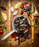 Fresh mussels in old colander with ingredients for tasty cooking on wooden background, top view. Stock Image
