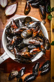 Fresh mussels in old colander on rustic wooden background, top view. Stock Image