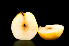 Fresh nashi pear and  cut on black background Royalty Free Stock Photography