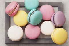 Fresh natural colorful macarons of different tastes in wooden frame, unusual abstract sweet art, gourmet picture. Fresh natural colorful macarons of different Stock Photos