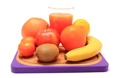 Fresh natural fruits and glass of juice on cutting board Royalty Free Stock Photos