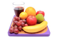 Fresh natural fruits and glass of juice on cutting board Royalty Free Stock Photo