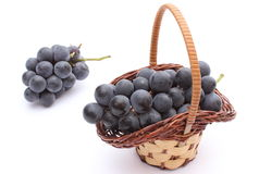 Fresh and natural grapes in wicker basket on white background Stock Image
