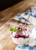 Fresh natural homemade yogurt on rustic wooden background. Fresh natural homemade yogurt with blueberru jam on rustic wooden background, copy space Stock Image